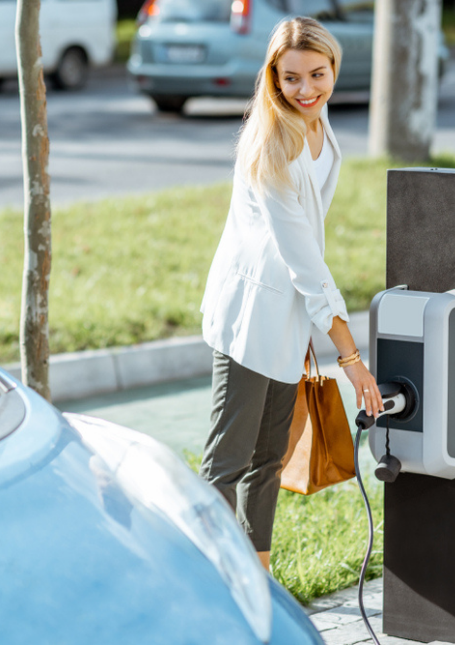Businesswoman plugging charging gun into the electric (resize)